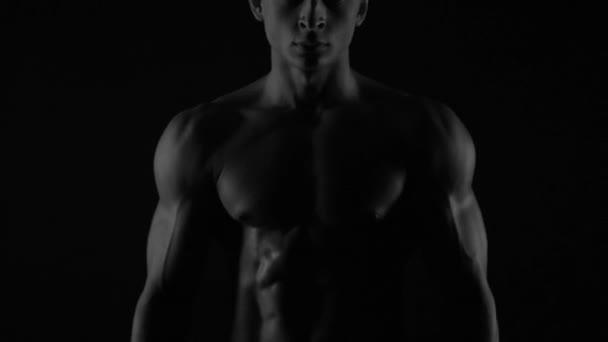 Silný kulturista pózování a školení v kontrastním světle ukazující jeho tělo a všechny svaly na něm pod vodou kapky a pomalé deště