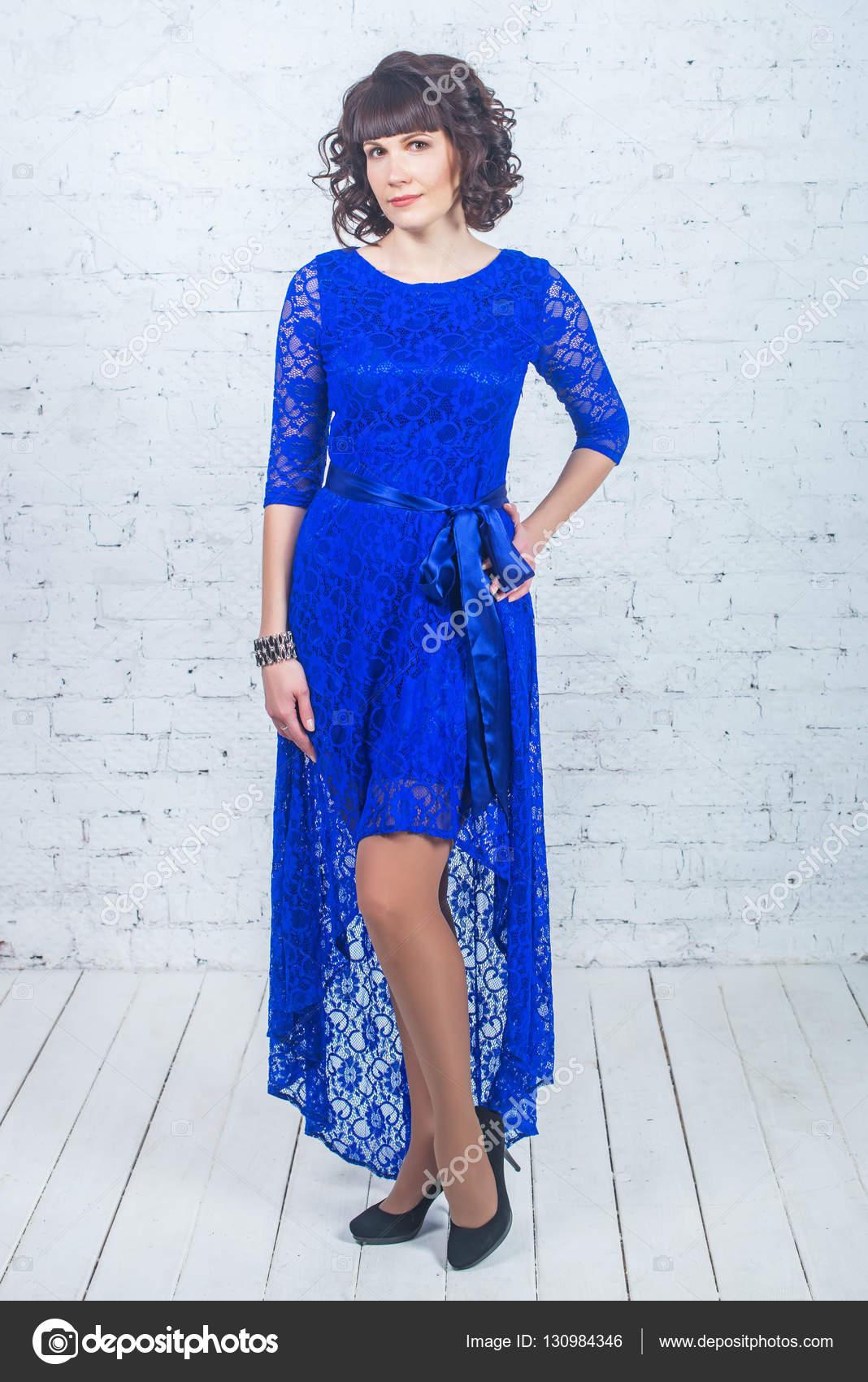 Junge schöne Frau blaues Kleid stehend vor weißem Hintergrund Mauer ...