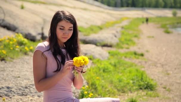 V létě. Romantická dívka v růžových šatech na břehu řeky obdivovat divoké květy pampelišky