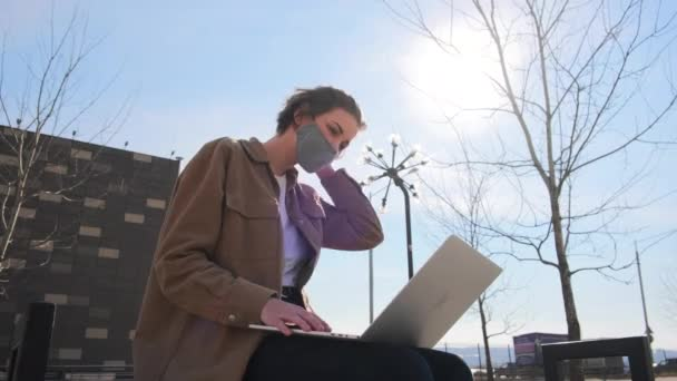 junge Frau in braunen Kleidern und Maske arbeitet mit einem Laptop im Freien auf dem Hintergrund der Stadt im Park