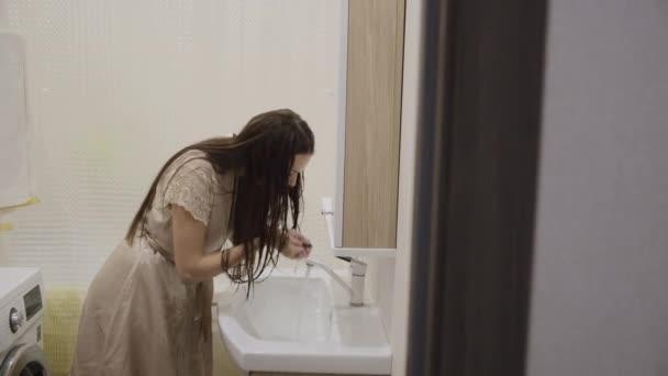 Fiatal barna lány hosszú sötét haj fényes ruhákban mosás szórakoztató és fogmosás otthon a fürdőszobában