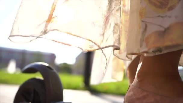 Dívka v šatech se vyvíjí z větru v blízkosti skútru