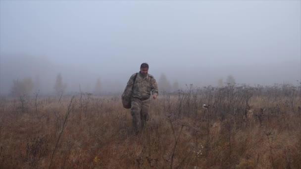 Egy kosaras férfi sétál át a mezőn a köd között.