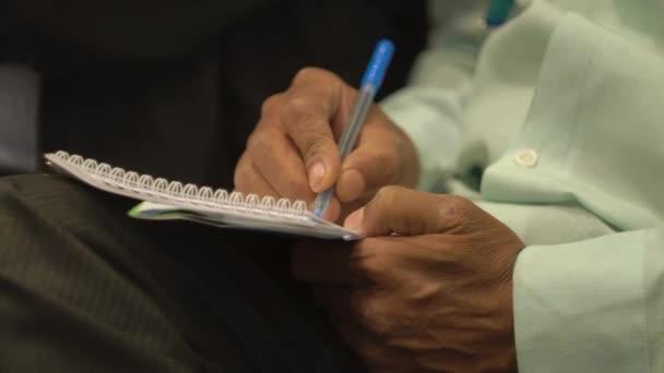 Az ember információkat ír egy üzleti előadásból egy jegyzetfüzetben.