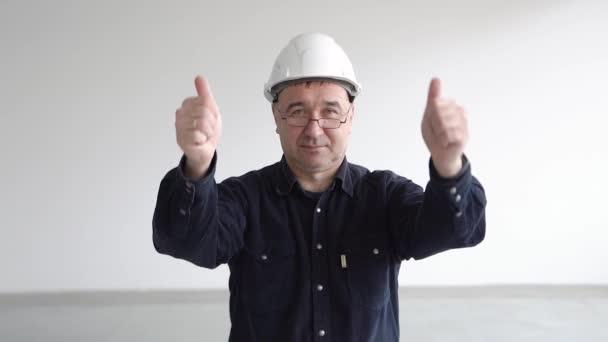 Ein Mann mit weißem Helm und Brille zeigt Daumen hoch mit beiden Händen und lächelt