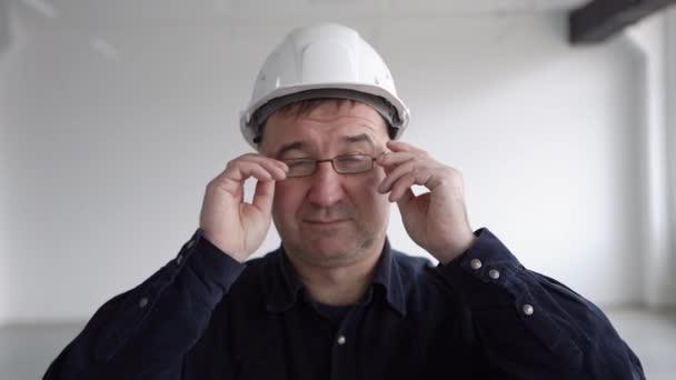 Ingenieur, Architekt im blauen Hemd, setzt eine Brille auf und lächelt