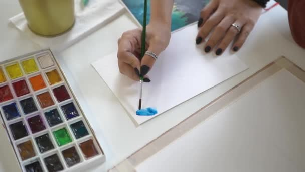 Girl draws with a brush and blue paint