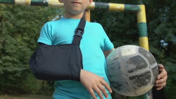 Active kid with injured arm in sling holding ball looking camera, sport injury