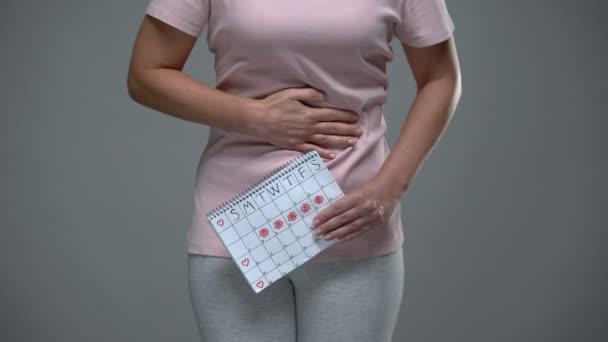 Dame, die ihren verkrampften Bauch berührt und Zeitrahmen-Kalender, weibliche Gesundheit, pms hält