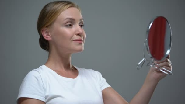 Atraktivní dáma obdivující její krásu v zrcadle, anti-aging kosmetika