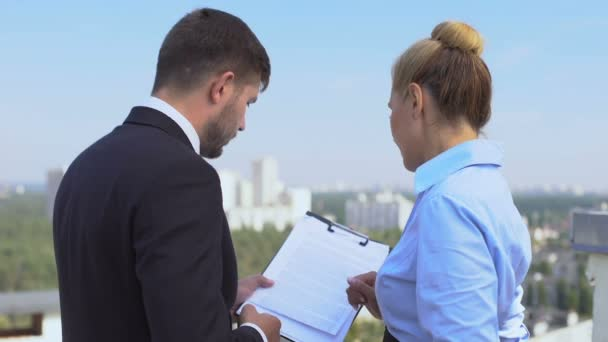 Male and female lawyers discussing contract details outdoor, office work, career