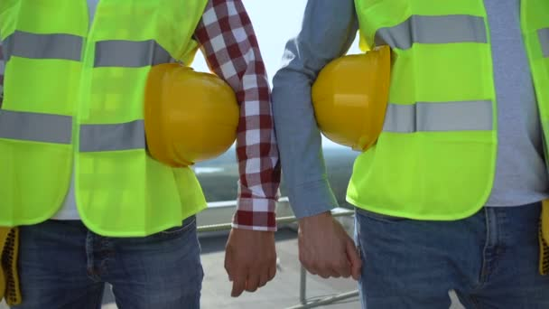 Männer in grünen Sicherheitsjacken mit Helmen, Sicherheitsregeln, Arbeitskleidung