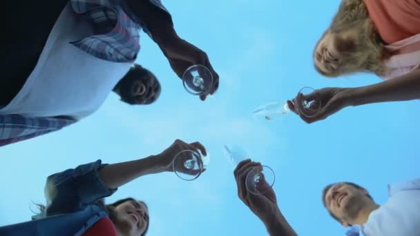 Base view of multiracial friends clinking champagne glasses, celebration