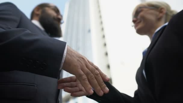 Male and female business partners shaking hands and smiling, successful project