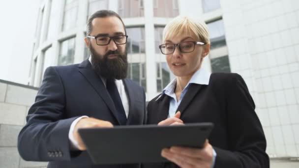 Obchodní partneři prohlížení prezentace projektu na tabletu, diskuse o spolupráci