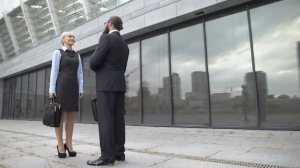 Man and woman shaking hands and smiling, business partners getting acquainted