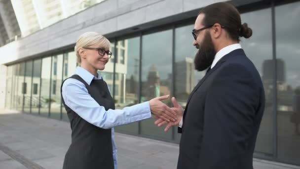 Business man bending to kiss female partners hand, woman displeased with sexism