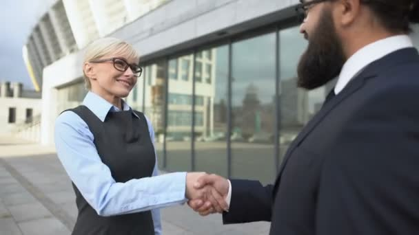 Satisfied male female business partners shaking hands, successful cooperation