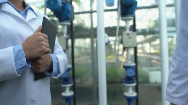 Muži a ženy inženýři v bílých pláštích potřásají rukou v továrně, spolupráce