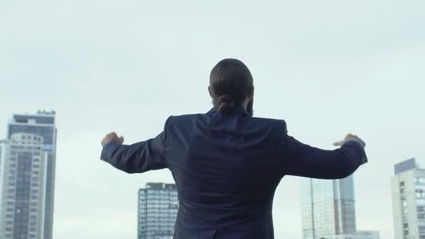 Cheerful male in business suit raising hands celebrating success, winner gesture