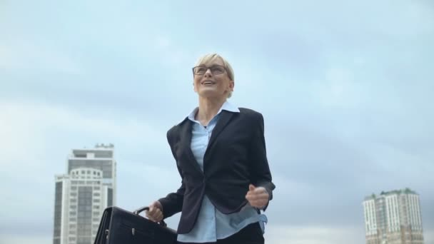 Happy woman in office suit holding bag and raising hands in victory gesture