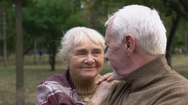 Starší muž a žena obdivující jeden druhého sedící na lavičce v parku, detailní záběr