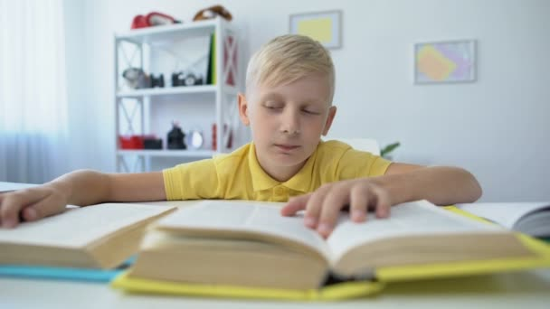 Bored schoolboy doing homework and reading books, upset kid touching head