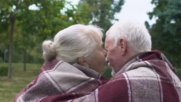 Elder couple sitting on bench under plaid, mature woman kissing man on cheek