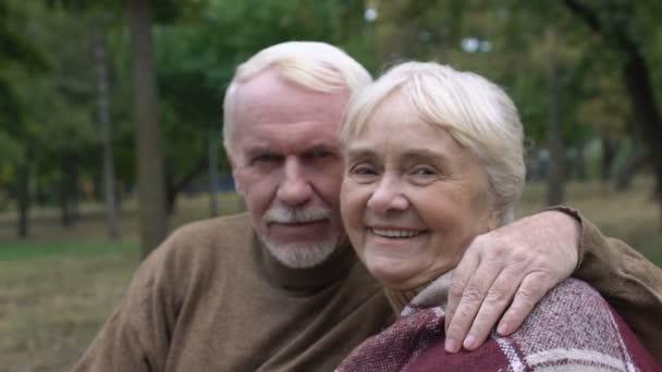 Starší manžel objímající svou dospělou ženu sedí na lavičce v parku pózuje na kameru