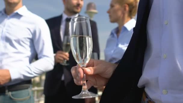 Podnikatelé drží sklenice na šampaňské, sledují prezentaci produktů společnosti