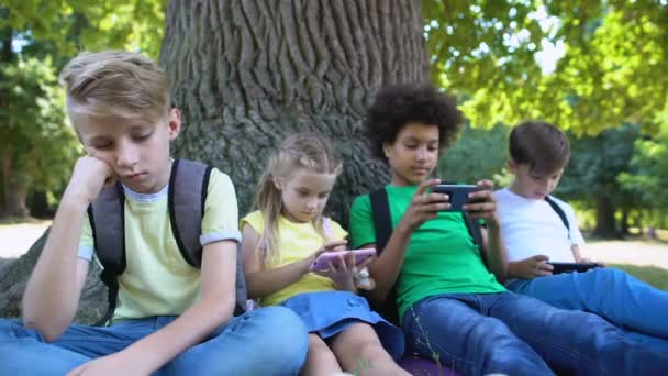 Boy feeling bored while friends playing games on phones instead of communication