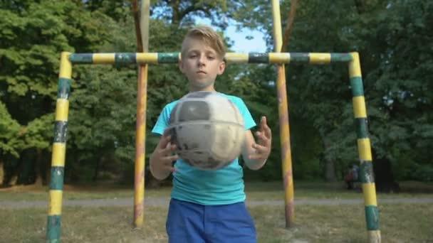 Vážný chlapec s fotbalem dívá do kamery na fotbalovém hřišti, pouliční zápas