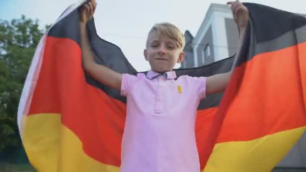 Patriot mladý chlapec mává německou vlajkou, slaví národní den nezávislosti