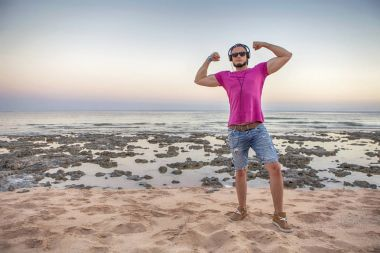 Sexy slim fit brunette man in blue jeans shorts and purple pink