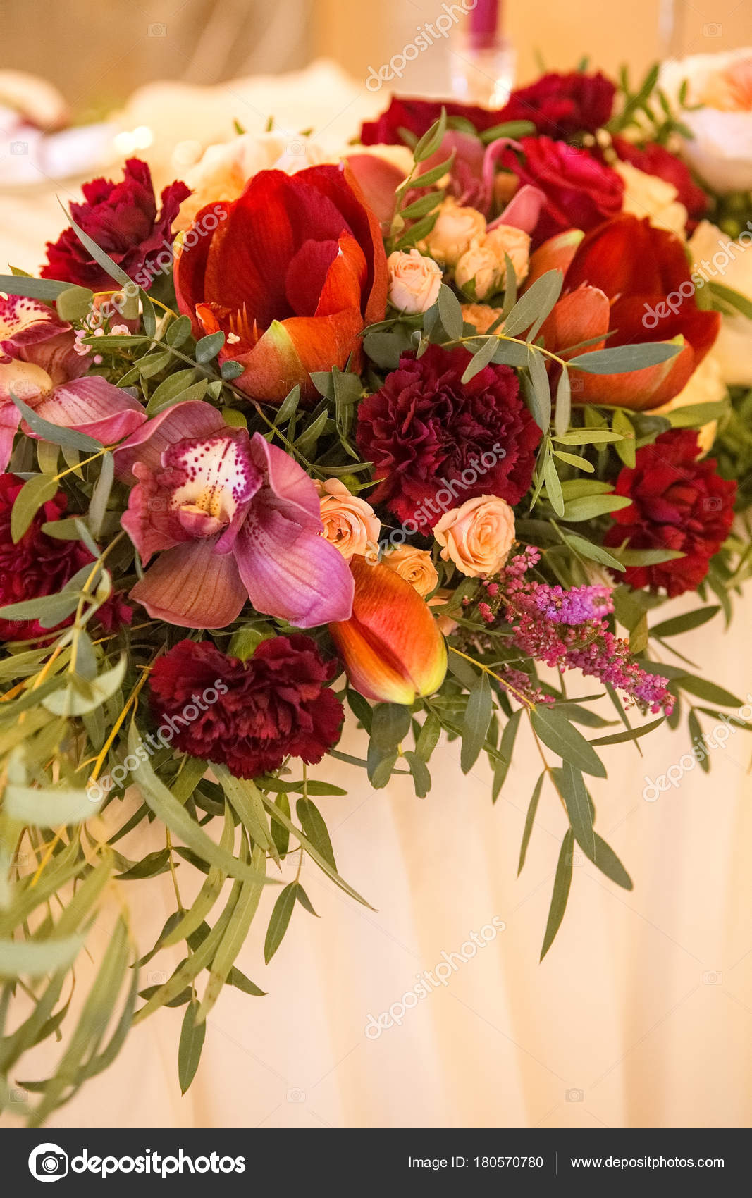 Wine color flowers on a wedding table surrounded by plates, tabl ...