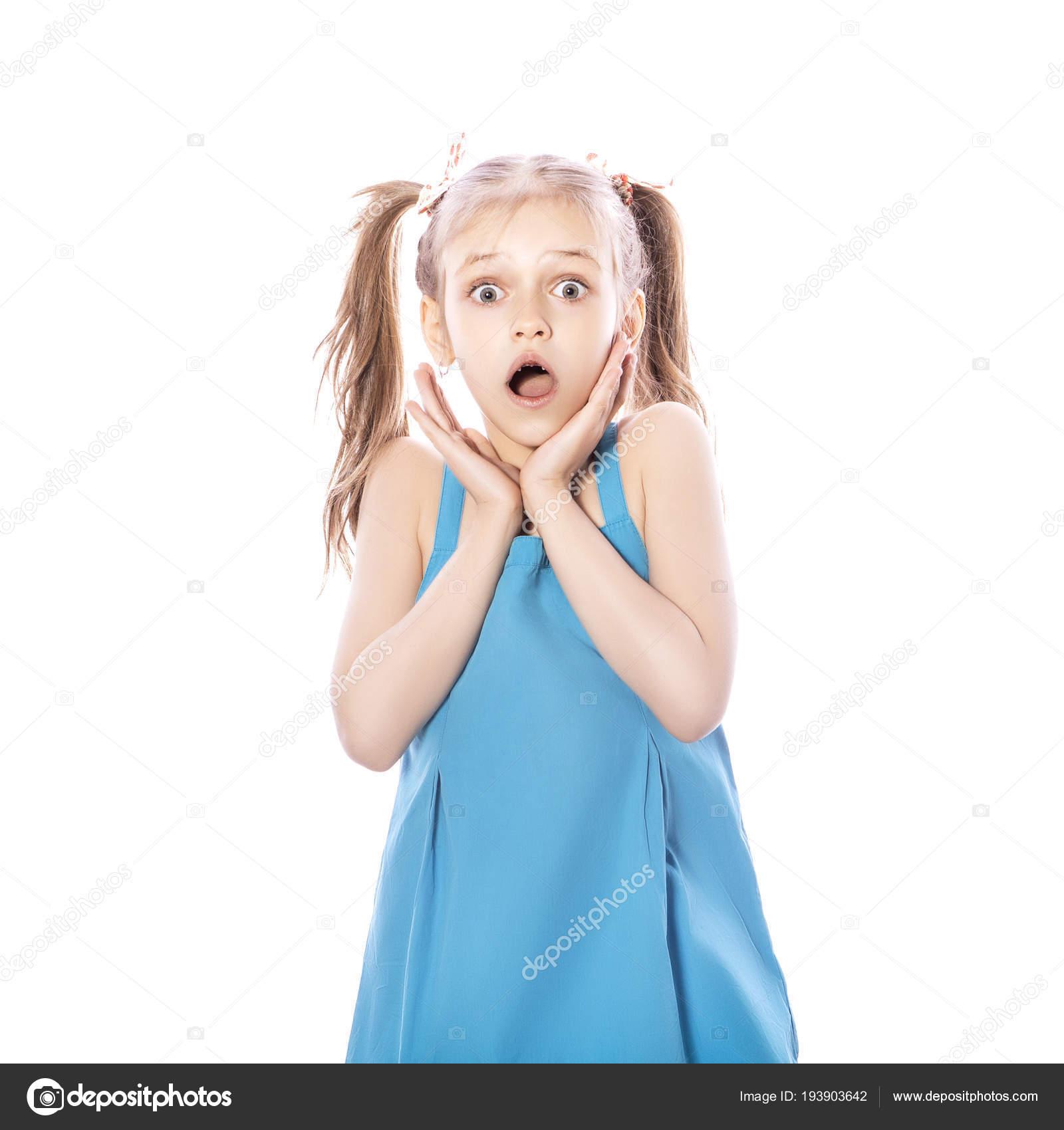 3cfde545f6ea Giovane ragazza bruna di sette anni in vestito blu su sfondo bianco isolato.  Stupore