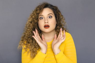 Cute brunette plus size woman with curly hair in yellow sweater and jeans standing on a neutral grey background. She amazed, shocked about some surprise stock vector