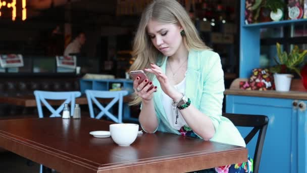 Woman in summer smart casual outfint sitting on a cafe terrace, drinking coffee and working in social media on her phone. Sexy cute smiling blonde posing and flirting on camera
