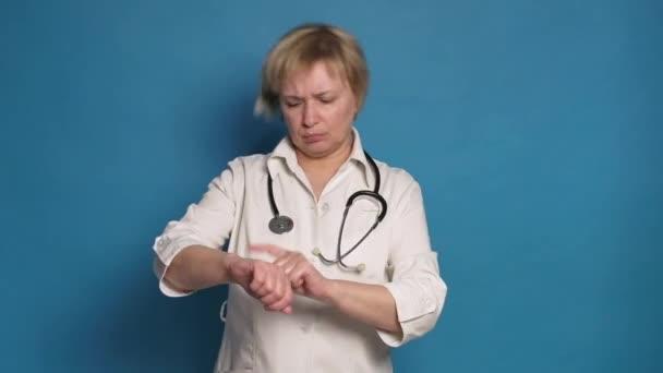 Starší bělošská doktorka v bílém plášti na modrém pozadí. Nosí stetoskop a dělá gesta ukazovat na hodinky