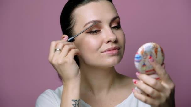 Sexy brünette kaukasische Frau in neutraler Kleidung, die auf rosa Hintergrund steht. Sie schminkt ihr Gesicht mit einem speziellen Pinsel. Kosmetisches Konzept