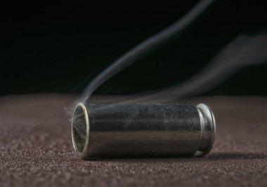"""Картина, постер, плакат, фотообои """"картридж для дробовика лежит на полу или на дороге. есть дым от гильзы, она недавно выстрелила """", артикул 319442402"""