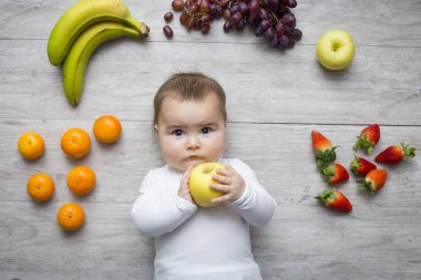 Little baby on the floor with colourful fruits