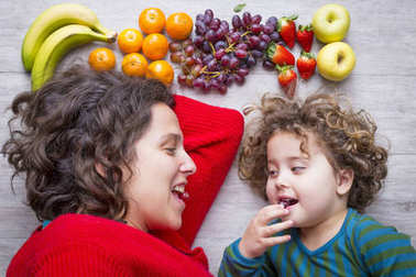 Mom and daugthter on the floor with colourful fruits