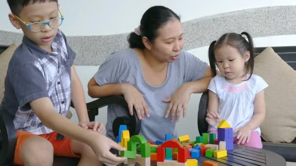 Malé děti a matka hraje s bloky na stole
