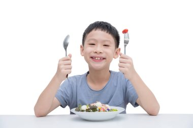 Young asian boy eating vegetables salad