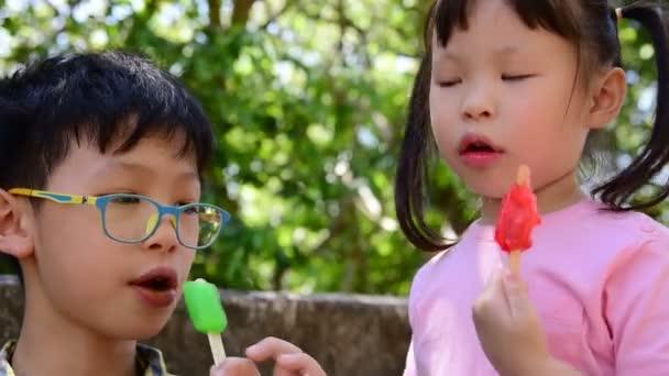 Malé asijské sourozenci spolu jíst zmrzlinu v parku
