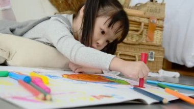 Little asian girl drawing picture by crayon and pencils on the floor at home