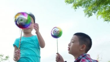 Little asian siblings playing with hand mill toy in meadow together