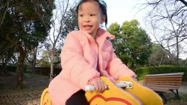Little asian girl playing and smiling on a horse swing in a green park playground, outdoors fun lifestyle.