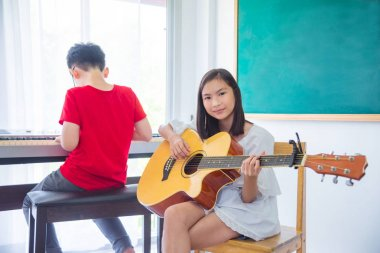 Beautiful girl playing guitar in classroom at school
